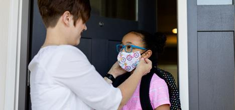 adult woman helping a female child with her face mask